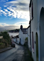 Looking downhill, narrow street, river, clouds, blue sky